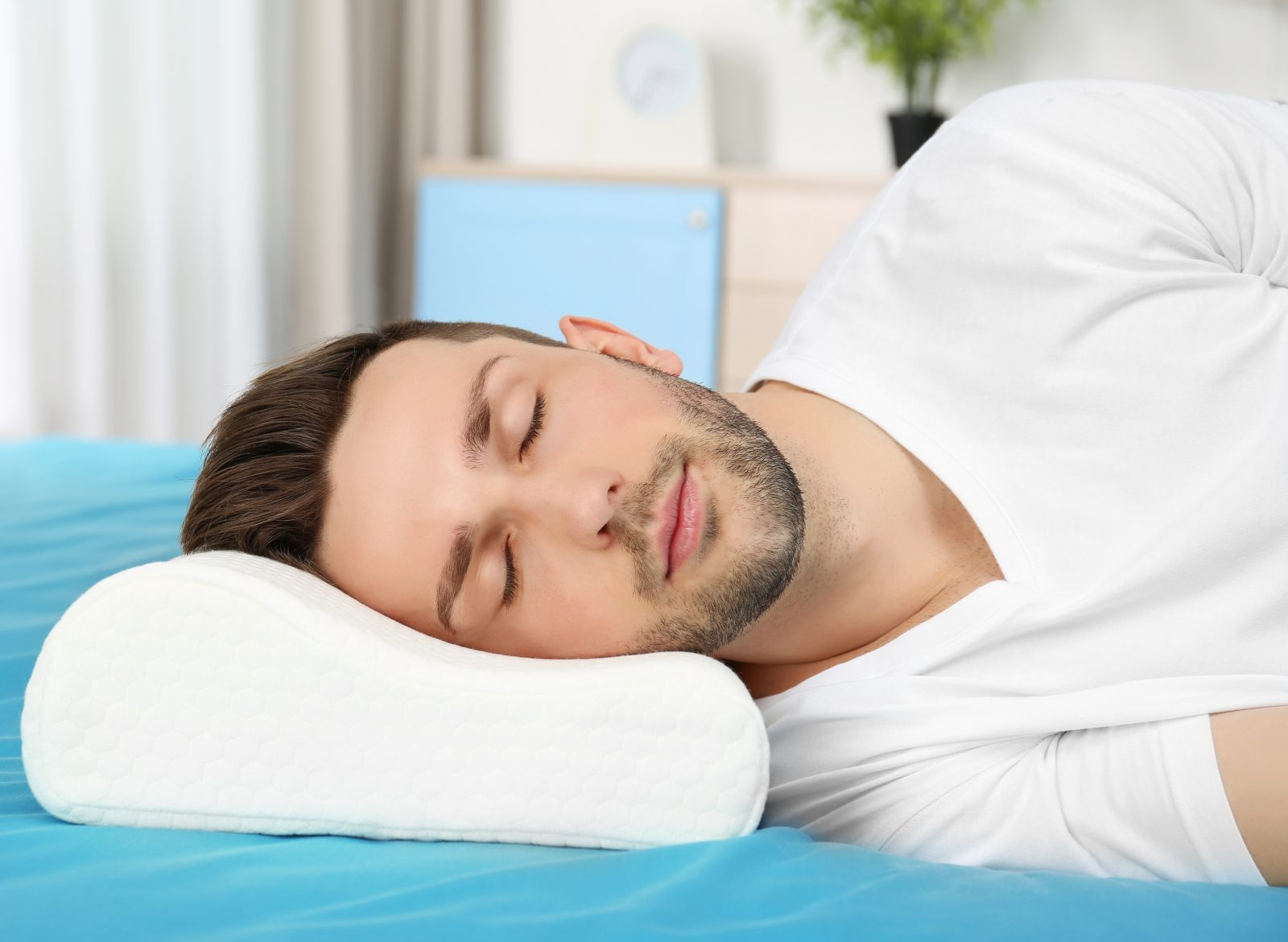 Young man sleeping on bed with orthopedic pillow at home. Healthy posture concept